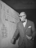Swiss Architect Le Corbusier Standing on Stage with Notes in His Hand and Drawing on Sketch Pad Premium Photographic Print