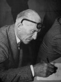 Swiss Architect Le Corbusier Leaning Down to Write with His Glasses Pushed Back on His Forehead Reproduction photographique