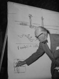 Swiss Architect Le Corbusier Standing on Stage with Notes in His Hand and Drawing on Sketch Pad Reproduction photographique