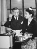 Woman Holding a Pan at a Small Oven While a Man Enjoys a Taste of the Dish with a Spoon Premium Photographic Print