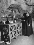 Priest Lighting a Candle in Catacombs in Rome Premium Photographic Print by Carl Mydans