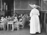 Young Children Watching a Nun Teach Class in a Welfare Center Premium Photographic Print