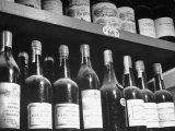 Dust-Covered Wine and Brandy Bottles Standing on Racks in a Wine Cellar Papier Photo