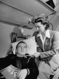 An Airline Stewardess Adjusting a Pillow for a Sailor on Leave Premium Photographic Print by J. R. Eyerman