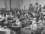 Children Sitting at their Desks in a Classroom, Teachers at the Rear of the Room Premium Photographic Print