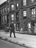 Children Watching a Policeman Walk His Beat in Front of Apartment Buildings Premium Photographic Print by Ed Clark