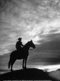 Silhouettes of Cowboy Mounted on Horse Premium Photographic Print by Allan Grant