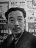 Portrait of Japanese Communist Sanzo Nozaka in Front of Wall of Party Posters Premium Photographic Print by Alfred Eisenstaedt