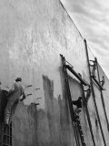 Men on Ladders Painting Exterior Wall of Building in Preparation for Opening of the World's Fair Premium fotoprint van Alfred Eisenstaedt