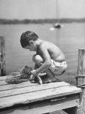 Small Boy Catching Fish with a Net Premium Photographic Print