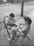 Young Boy and Girl Sitting in Folding Chairs While Playing Cards on Sidewalk Impressão fotográfica premium por Alfred Eisenstaedt