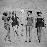 Four Models Showing Off the Latest Bathing Suit Fashions While Lying on a Sandy Florida Beach Fotografisk tryk af Nina Leen