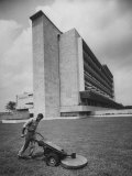 Man Mowing Grass Near New Hospital Premium Photographic Print