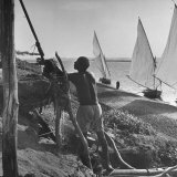 Man Working with Irrigation System as Sailboats Sit at Edge of Nile River at Wadi Halfa Photographic Print