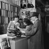 Woman Working in a Record Store, Showing Items to Customers Photographic Print