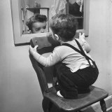 Little Boy Standing on Chair to See Face in Mirror Photographic Print