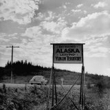 Road Sign Showing the Dividing Line Between Alaska and the Yukon Territory Photographic Print by J. R. Eyerman