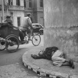 Staving Beggar Boy Sleeping While a Rickshaw Speeds on by Him Photographic Print