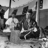 Japanese Swordmaker Making a Samarai Sword as Shinto Priest Looks On Photographic Print by Margaret Bourke-White