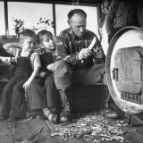 Grandfather Oscar Risser Is Whittling a Wooden Knife for His Grandchildren Who Watch Intently Photographic Print