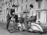 Two Men Talking in Street with Vespa Scooter and Bicycle Lámina fotográfica por Dmitri Kessel