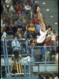 Soviet Gymnast Olga Korbut in Action on the Uneven Bars at the Summer Olympics Kunst på metall av John Dominis