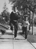 Tennis Player Pancho Segura Running with His Younger Son Premium Photographic Print by Ralph Crane