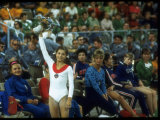 Soviet Gymnast Olga Korbut Holding Up Flowers at the Summer Olympics Premium Photographic Print by John Dominis
