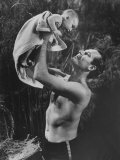 "Actor Charlton Heston Lifting Son Fraser, Portraying the Baby Moses, in ""The Ten Commandments"" Premium Photographic Print by George Silk"