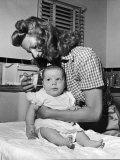 Actress Rita Hayworth, Brushing Her Baby's Hair Premium Photographic Print by Peter Stackpole