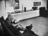 Architect Mies Van Der Rohe Relaxing on Couch While Smoking Cigar and Reading at Home Premium Photographic Print