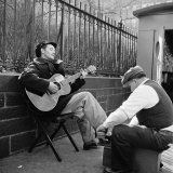 Folk Singer Woody Guthrie Palying His Guitar While Getting a Shoeshine Premium Photographic Print