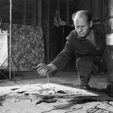 Painter Jackson Pollock Squatting on Floor, Applying Sand to Canvas, in Long Island Premium Photographic Print by Martha Holmes