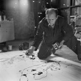 Painter Jackson Pollock Smoking as He Squats on Floor Applying Paint to Canvas, Long Island Studio Premium Photographic Print by Martha Holmes