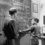 Young Boy Working Out a Math Problem with Help of Instructor at Orphanage Premium Photographic Print by Tony Linck