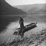 A Man Standing in a Rowboat on the New River Premium Photographic Print by John Phillips