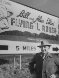 Super Rich Texas Millionaires William Likins Standing in Front of Sign at Main Entrance to Ranch Premium Photographic Print by Michael Rougier