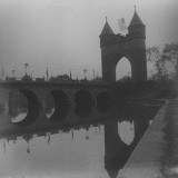 A Bridge with a an Arched Double Tower at One End of It Premium Photographic Print by Wallace G. Levison