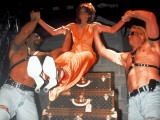 Actress Sandra Bernhard Lifted by Men From Stacked Louis Vuitton Trunks at Centennial Party Premium Photographic Print by Dave Allocca