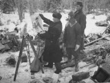 Finnish Soldiers Looking at a Patriotic Poster Left Behind by Defeated Russian Troops Premium-Fotodruck von Carl Mydans