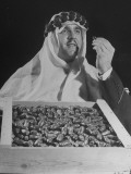 Man Dressed in Arabic Clothing Holding Crate of Dates During Date Festival Premium Photographic Print by Loomis Dean