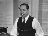 Writer Robert Benchley, Sitting at His Desk with a Small Wade of Paper in His Mouth Metal Print by Bernard Hoffman