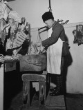 A Butcher Working in the Hungarian Meat Shop Premium Photographic Print by John Phillips