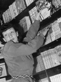 A Young Woman Selecting a Book from the Communist Library Premium Photographic Print by Paul Dorsey