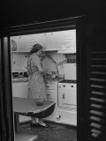 Woman Pouring Drinks in Her Kitchen of Her Trailer Premium Photographic Print by Martha Holmes
