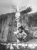 A Liitle Igorot Boy Squating and Laughing in Front of the Street Sign Premium Photographic Print