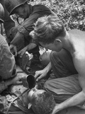 Badly Wounded Medic Being Given Water While Soldier in Background Cuts Clothing from His Wounds Premium Photographic Print