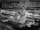 Man Whose Wife Is Being Treated for Polio Standing in their Family Grocery Store Premium Photographic Print