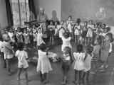 Black Teacher Leading Children in Dancing to Nursery Rhymes in Class at the National War Memorial Premium Photographic Print
