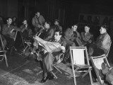 Songwriter Irving Berlin Reading Newspaper as Others Sit around Talking Premium Photographic Print